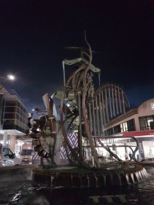 Nighttime, Hornsby. A large metal statue and fountain is odd-looking, featuring a water mill and pipes