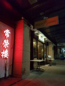 夜间,广州府的外部有粤语的霓虹红色标志,陷阱被点燃。
