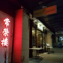 Night time, the exterior of House of Canton includes Cantonese writing in neon red sign and the entrace is lit up