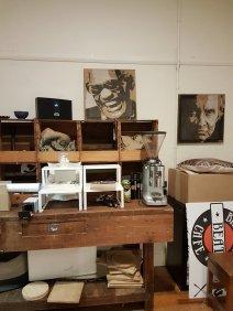 在咖啡馆里。一张木制桌子,有各种敞开的抽屉,上面有咖啡袋和咖啡机。墙上有雷·查尔斯和约翰尼·卡什的照片