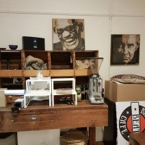 Inside a cafe. A wooden desk with various open draws showing coffee sacks and a coffee maker. Images of Ray Charles and Johnny Cash on the walls