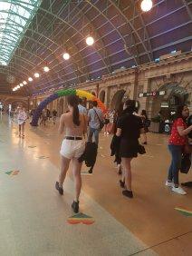 人们在大中央车站散步和聊天,悉尼。有一个由骄傲旗颜色做成的气球拱门。