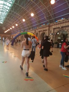 People walk and talk at the grand Central Station, Sydney. There is an arch of balloons made in the pride flag colours
