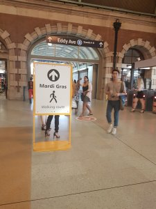 """People walk in the background inside the grand Central Station. A sign shows an arrow and a person walking. It says: """"Mardi gras walking route."""" In the background is the Eddy Ave exit sign"""