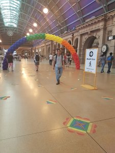 A man walks in the middle-grown wearing a backpack. In the background is a large arch made from balloons meant to evoke the Pride Flag