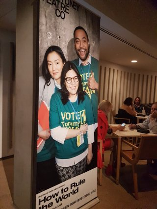 Large poster shwing three people of colour: Aboriginal woman and playright Nakkiah Lui wearing black glasses, an Asian woman (Michelle Lim Davidson) and a Togan man (Anthony Taufa). Theatre goers can be seen sitting at tables in the background
