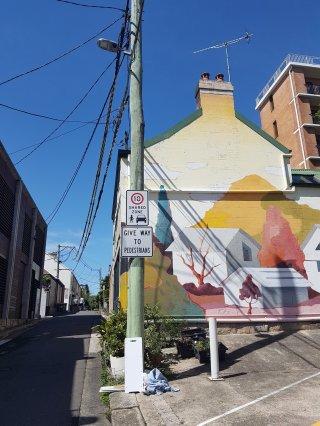 Street art takes up the entire side of a large building. Features beautiful pastel and muted colours of yellow, red and white. Small white houses have red and purple trees growing out of them, and yellow and lime hils are in the background. There is a discarded cloth in the foreground beneath a 'Give way to pedestrians' sign