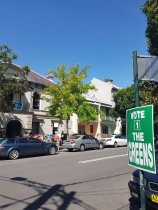 A green and white sign in the foreground says: Vote 1 The Greens. In the background is the Redfern Town Hall, which looks like a large house. Cars and various sign are out the front