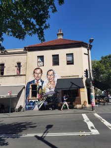 Taken from across the road, street art adorns a large building and cafe. It shows Australia's former Prime Minister, Tony Abbott, drawn in a suit and he is also in a white bridal gown with lipstick. He is infamously homophobic and opposed to marriage equality