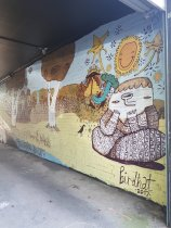 Streetart in Redfern. A mural shows a large fantastical brown and yellow landscape with trees and smiling stars and sun. A person sits cross-legged, with an upside-down nose that looks like a drain