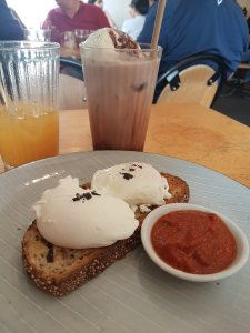 Hunter's Corner all-day-breakfast. In the foreground, one piece of soudough has two poached eggs with black pepper, and a side red sauce. In the background is a half-drunk orange juice and iced chocolate. People can be seen in the distance