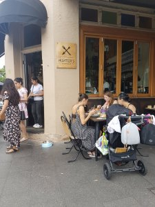 A corner cafe. South Asian women are walking out, while White and Asian women sit together eating out the front, with their pram