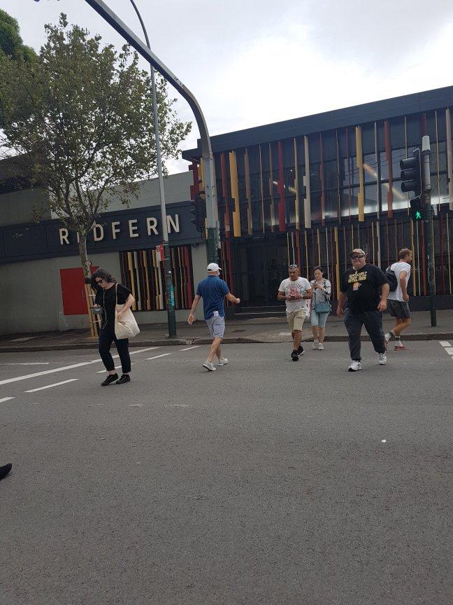 雷弗恩车站入口有一个大字:雷弗恩。黄色、红色和棕色的薄矩形装饰着外部。人们走过马路