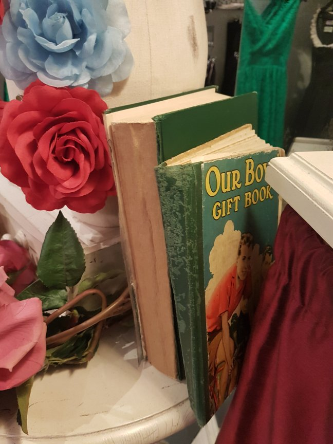 Close up of old, tattered books, one is green and shows a 1950s drawing of a White boy outdoors. The cover says: Our boy gift book. Red, blue and pink flowers srround the display