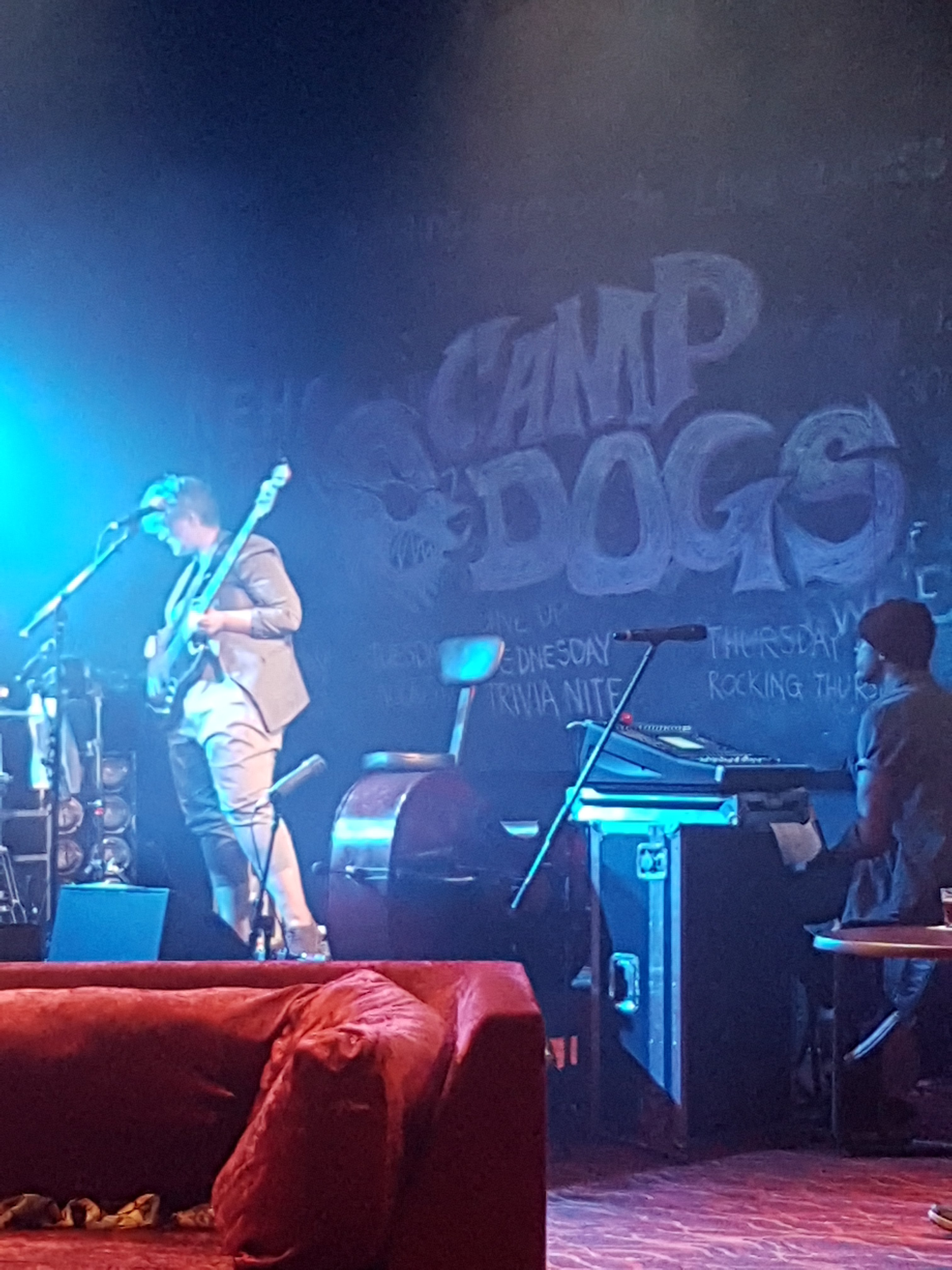 A White-presenting woman with short hair and a suit jacket is playing on a bass guitar. An Aboriginal man is wearing a beany and sits behind a keyboard. The sign in the background shows a drawing of a large dog's face wearing sunglasses. The sign is drawn in chalk and says: Barbara & the Camp Dogs. A red velvet couch is in the foreground