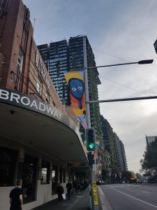 Corner of a street. White man walking in foreground and other people walk in the background. There is a poster high above the lights showing a mirror with a blue face and red eyes, the symbol of the Sydney Writer's Festival 2019