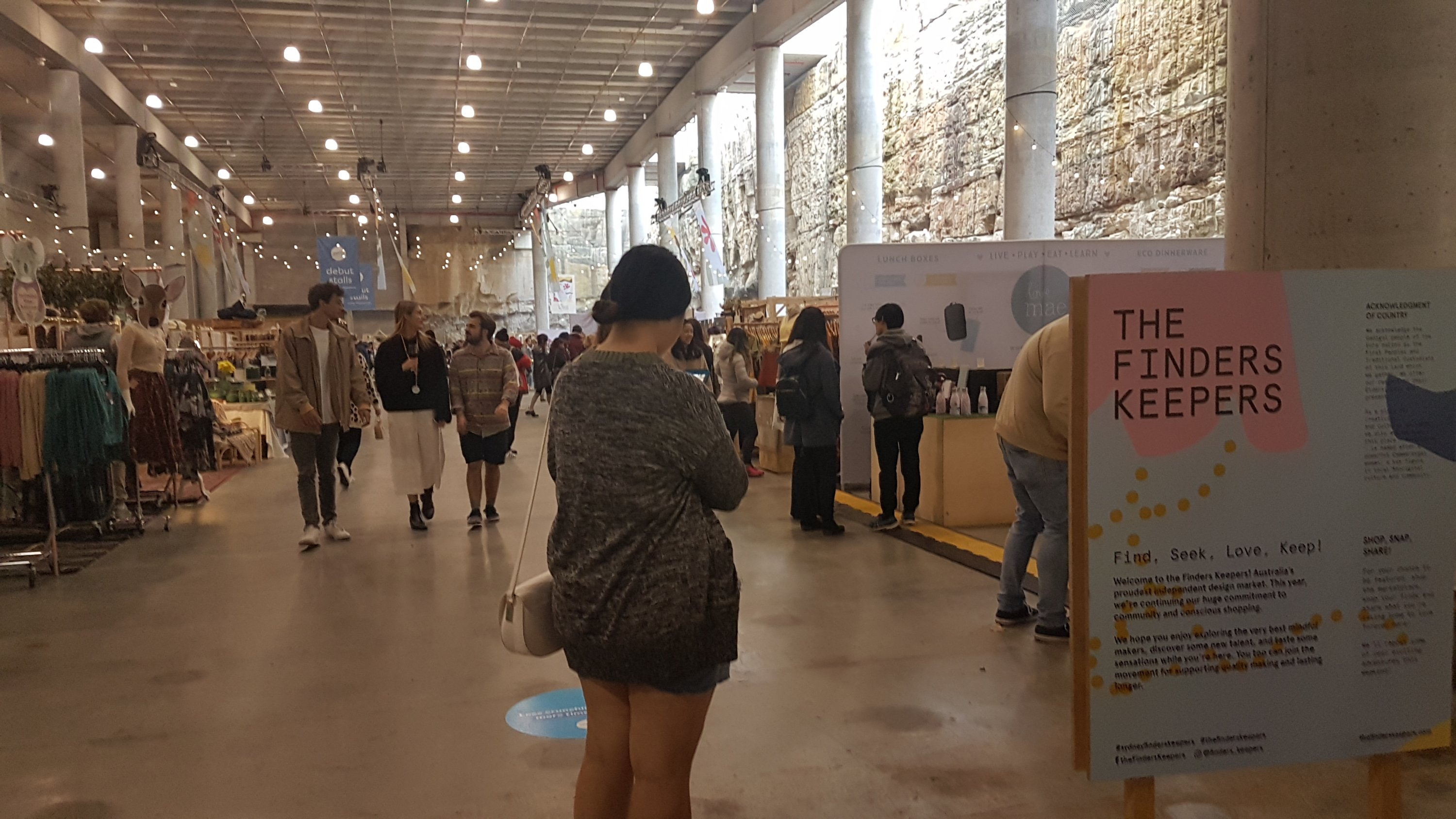 A woman stands at the entrance to Finders Keepers. In the background are other people walking near clothing racks and other stalls