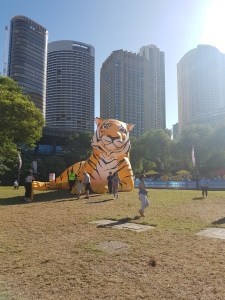 A yellow and black-striped tiger lays out on a lawn. The tiger lantern's size is in contrast to the bankground of skyscrapers - at half their size, with people looking diminutive in comparison in the middle groun=d