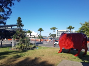 A red metal merino sheep stands at 2.5 meters, in the mid-ground, surrounded by trees, near the Oversas Passanger Terminar, and the Sydney Opera House in the far background