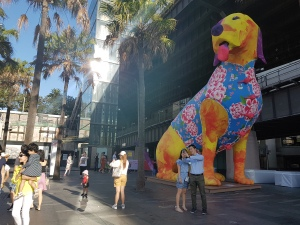 Standing at quadriple the size of the average person, the giant yellow dog has its red tongue hanging out. It sits on its hind legs, propped up by its front legs, its chest out. It is wearing a blue cheongsam, decorated with beautiful red and white flowers