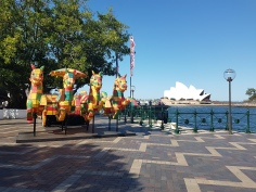 Four hourses in multicoloured yellow, red and green blocks are in the background, arranged as a chariot, which children could climb into. In the background is the massive Sydney Opera House and the water