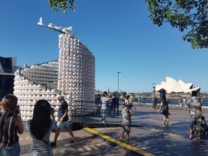 People in the foreground take photos of a large white sculpture, which on closer inspection is made of hundreds of white pig faces with pink noses and ears, and in other places, pig bums with pink curly tails. The sculpture is immersive, and you can walk around the inside in a circle. The Sydney Opera House can be seen in the background on a sunny day