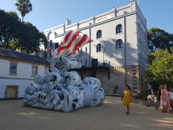 A white and red stripped ox has its head down and seems to be charging forward atop a grey and black marble set of waves, representing the scholar's rock. People walk in the middle background, against the sculpture three times their size, in a book in front of other buildings