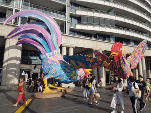 Two brighly plumaged roosters have their wings spread out in a dance fight. People talk past mostly ignoring the plucky eight-metre warriors in the busy Circular Quay outdoors shopping and restaurant district
