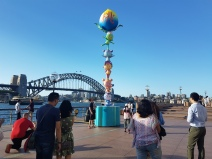 People stand in the foreground, waiting patiently and respectfully for a turn to take their photo with a tower of five cute, brightly-coloured monkeys standing on top of one another's heads. In the background is the iconic Sydney Harbour Bridge against a clear, blue-sky. The monkeys are juggling a gaint blue and yellow peach at the top of their primate tower