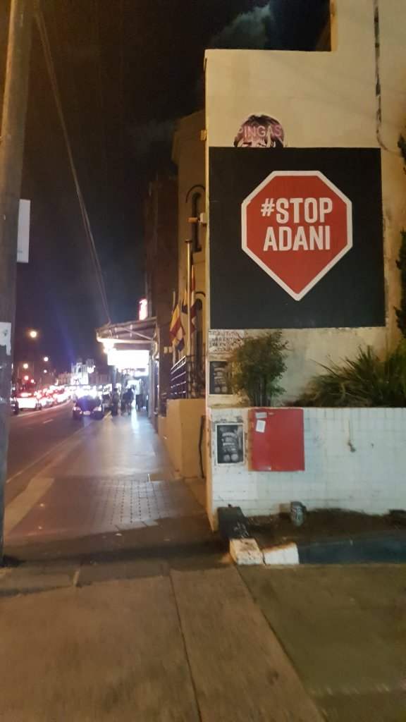 "Night time street. A large poster on the side of a building is in the shape of a red ""stop"" sign. It reads #STOP Adani"