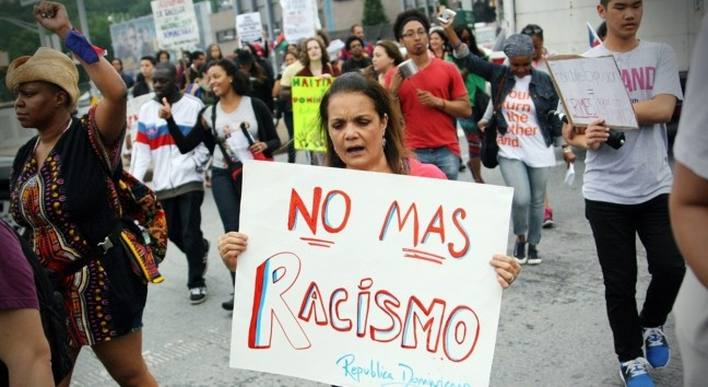 Protesters hold signs on the str4eet. One Brown woman is chanting and her sign says: No mas racismo Republica Dominicana