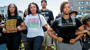 The three #BlackLivesMatter co-founders are walking with their arms interlocked. They stare with determination at the viewer. Tometi on the left wears a black BLM t-shirt. Garza in the cetre wears a white BLM t-shirt. Cullors on the right wears a t-shirt that says 'bullet proof.'