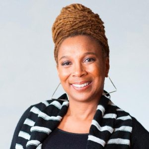 Prof Kimberlé Crenshaw is smiling. Her hair is worn high in a bun and she wears beautiful large earrings