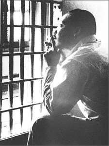 Martin Luther King Jr stares out of a jail cell. He is bathed in light. He has his elbows resting on his knees and his hands on his chin. He looks up and is pensive