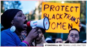 A Black woman yells into a megaphone. In the background is a yellow sign with black writing that partially reads: Protest Black