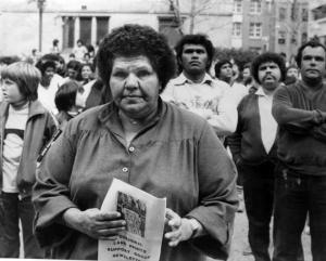 Black and white photo of Coleen Shirley Perry Smith stares with determination at the audience. She is dressed in a large shirt. She holds a poster that reads: Aboriginal land rights support group newsletter. Other Aboriginal people stand in the background