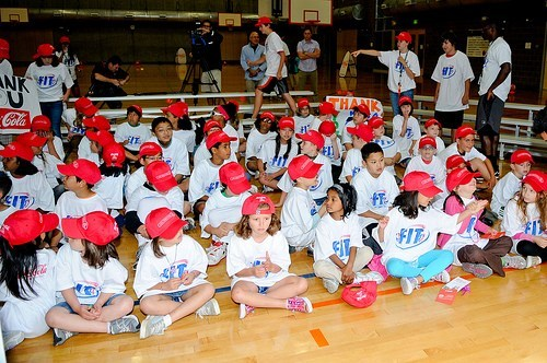 Children of various backgrounds sit on the ground of a gym. They wear white t-shirts with the word 'FIT' on the front, as well as red hats