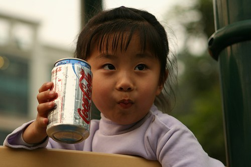 Asian girl drinks a can of coke