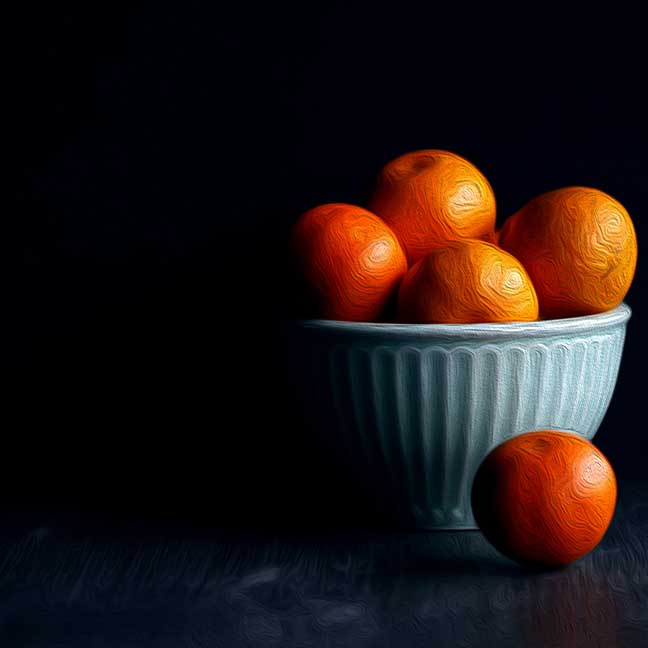 White bowl with oranges against a black background