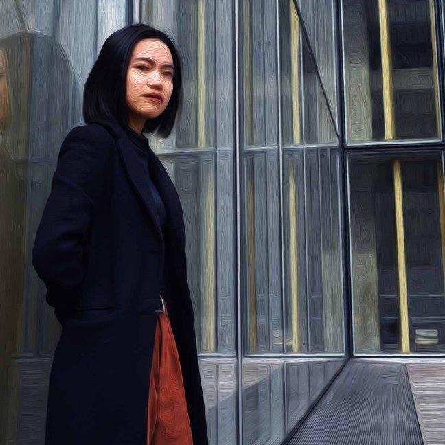 一位亚洲妇女站在一座玻璃建筑旁的画像。她的脸模糊了