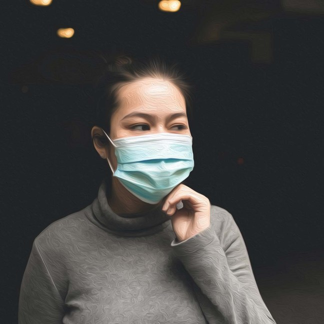 An Asian woman wears a surgical mask. She's touching her hand to the bottom of her chin as she looks off to the side