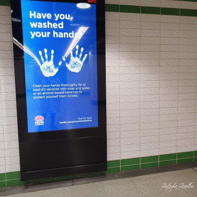 Oil painting of a subway sign about COVID-19. It shows an imprint of two hands. The message reads: have you washed your hands?