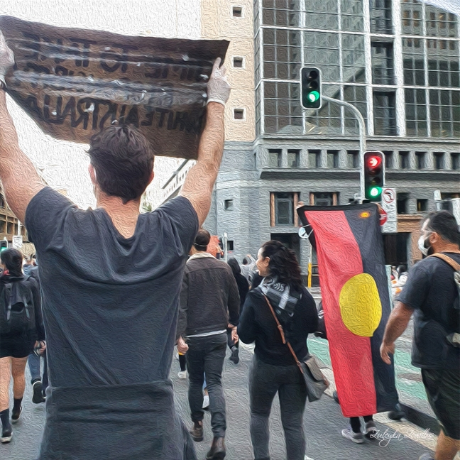 People march during the Black Lives Matter protest in Sydney. One man holds up a sign. Another person holds up a large Aboriginal flag