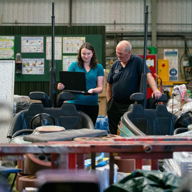 A young white woman stands next to an older white man in an industrial workshop. They are both smiling looking at her laptop