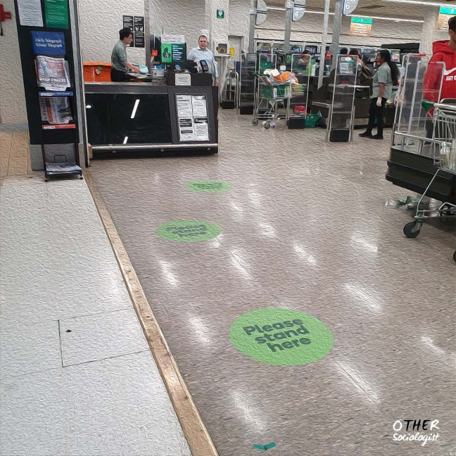 """Entrance to a supermarket. Stickers on the ground say """"please stand here."""" Workers are busy in the background"""