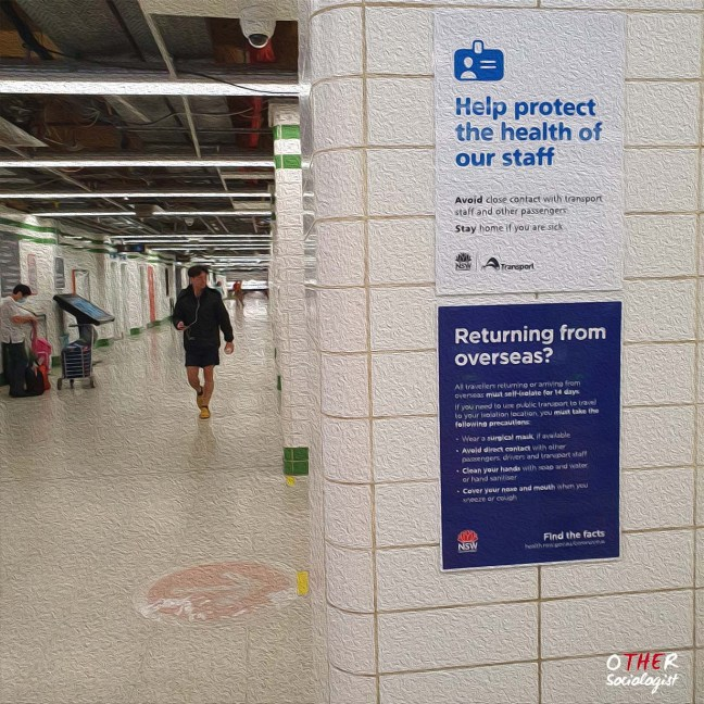 """A person walks in the distance inside Central Station in Sydney. Two COVID posters say: 1 """"help protect staff,"""" and 2) """"returning from overseas?"""""""