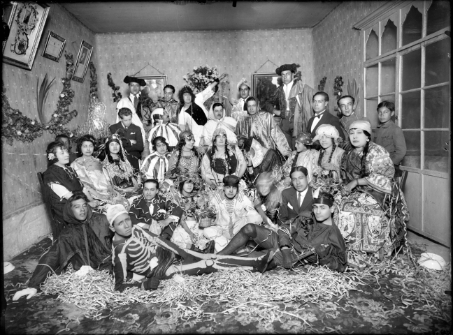 Two dozen mestizo people pose for a photo dressed in costumes. One is dressed as a skeleton