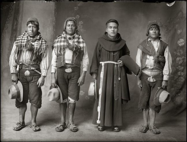 A mestizo priest stands in between three Quechuan men