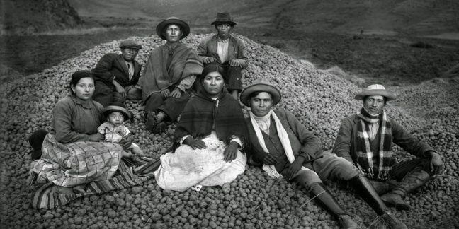Quechuan family sit on a mound of rocks
