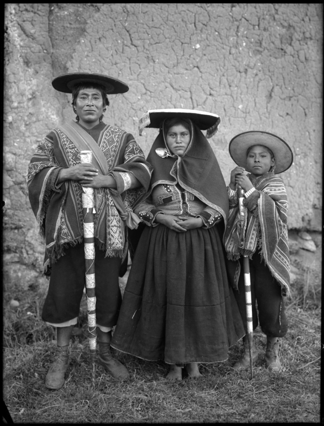 Quechuan man, woman, and child holding traditional walking sticks